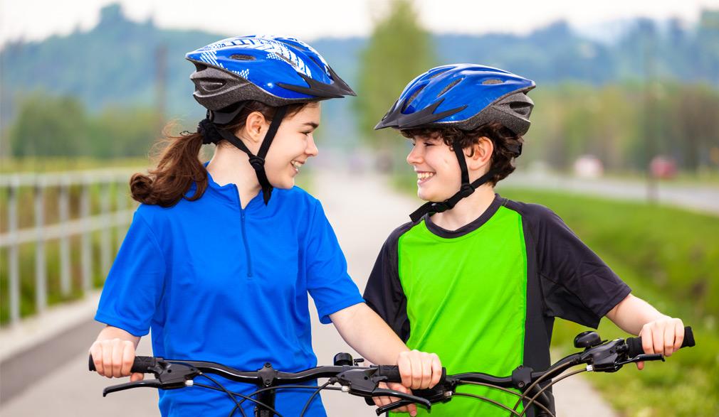 Ados se regardant, installés surs leur vélos avec leur casque sur la tête | Défi Tête la Première
