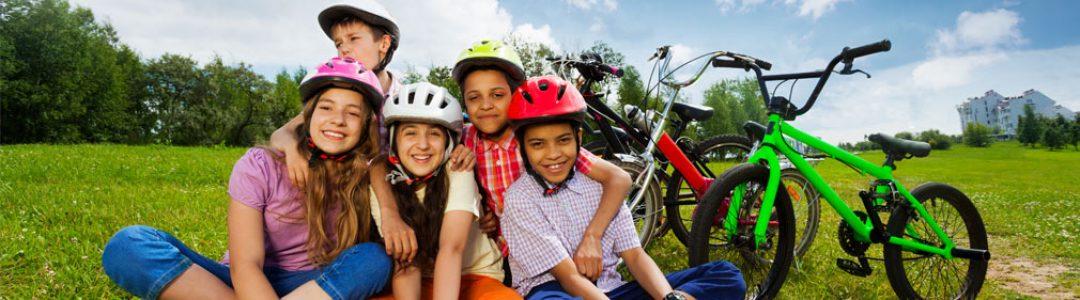Groupe divers d'adolescents assis dans l'herbe devant leurs vélos, avec leur casque sur la tête | Défi Tête la Première