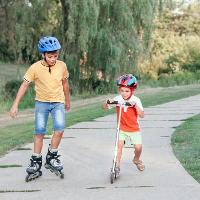 Frères portant des casques de protection se promenant en patin à roues alignées et en trottinette | Jamais sans mon casque